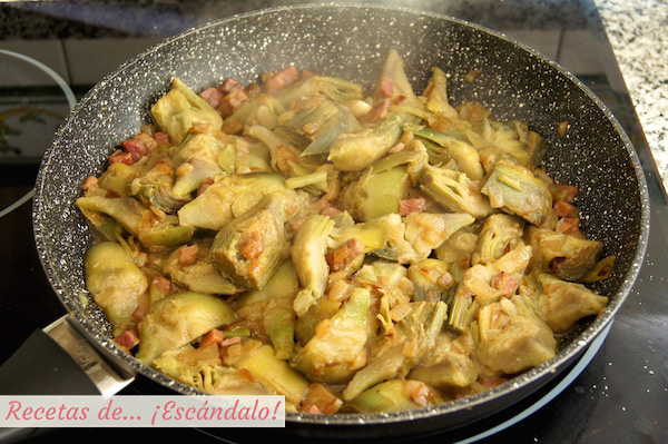 Saltear las alcachofas con el jamon, la cebolla y los ajos